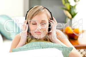 Relaxed blond woman listening music lying on a sofa