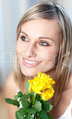 Portrait of a charming woman holding yellow roses