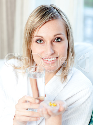 Sick caucasian woman holding a glass of water and pills