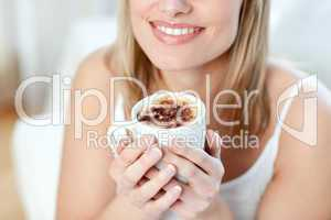 Close-up of a cheerful woman drinking a coffee