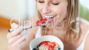 Charming woman eating muesli with fruits