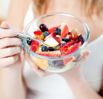 Close-up of a woman eating a fruit salad