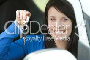 Brunette teen girl sitting in her car holding keys