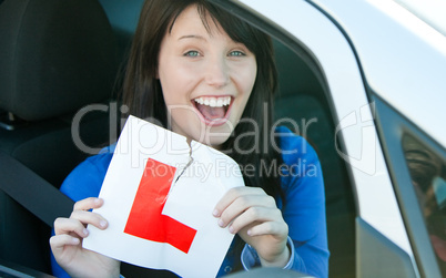 Happy brunette teen girl sitting in her car tearing a L-sign