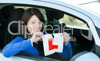 Joyful teen girl sitting in her car tearing a L-sign