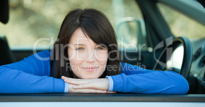 Cute teen girl smiling at the camera sitting in her car