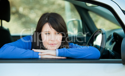 Attractive teen girl smiling at the camera sitting in her car