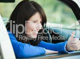 Smiling teen girl with a thumb up sitting in her car