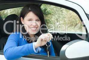 Happy teen girl sitting in her car holding keys