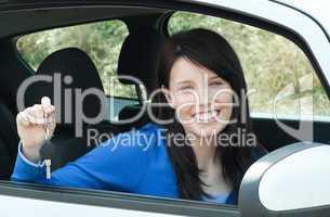 Jolly teen girl sitting in her car holding keys