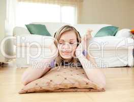 Attractive woman listening music lying on the floor