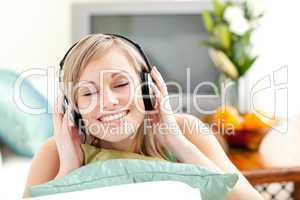 Delighted young woman listening music lying on a sofa