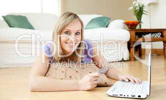 Cheerful woman shopping on-line lying on the floor
