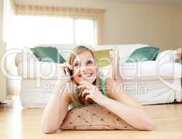 Joyful young woman talking on phone lying on the floor