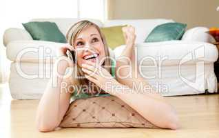 Laughing young woman talking on phone lying on the floor