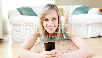 Joyful woman sending a text lying on the floor