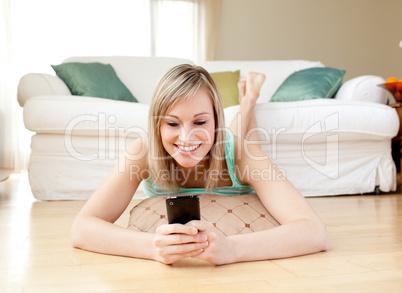 Jolly woman sending a text lying on the floor