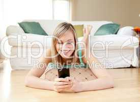 Jolly woman sending a text lying on the floor
