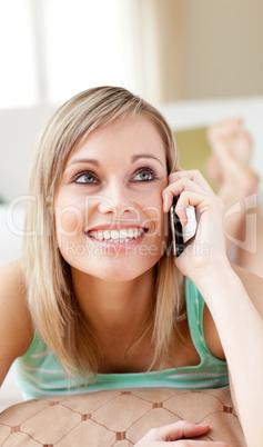 Joyful woman talking on phone lying on the floor