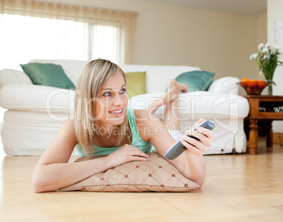 Beautiful blond woman watching TV lying on the floor