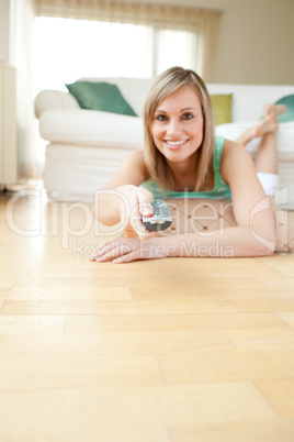 Pretty young woman watching TV lying on the floor