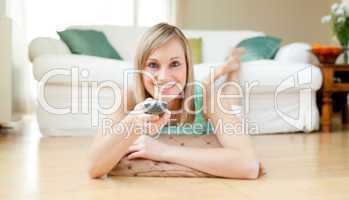 Blond young woman watching TV lying on the floor