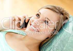 Jolly young woman talking on phone lying on a sofa