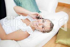 Bright young woman talking on phone lying on a sofa