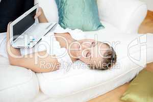 Relaxed young woman surfing the internet lying on a sofa