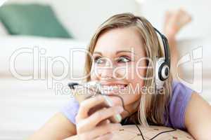 Cheerful woman listening music lying on the floor