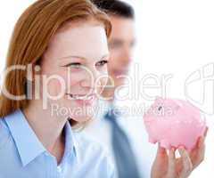 Smiling businesswoman holding a piggybank