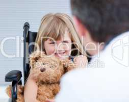 Smiling little girl sitting on the wheelchair with her teddy bea