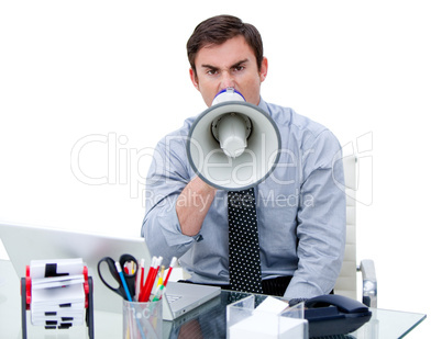 Furious businessman yelling through a megaphone sitting at his d