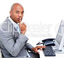 Confident businessman asking for silence sitting at his desk