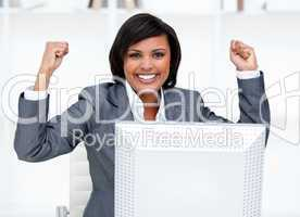 Confident businesswoman punching the air in celebration