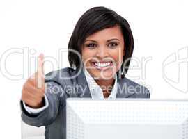 Cheerful businesswoman with a thumb up working at a computer