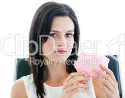 Beautiful businesswoman holding a piggybank and looking at the c