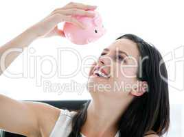 Cute businesswoman looking at a piggybank