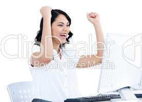 Positive  businesswoman punching the air in front of her compute