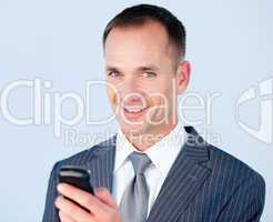 Confident businessman sending a text with his  phone