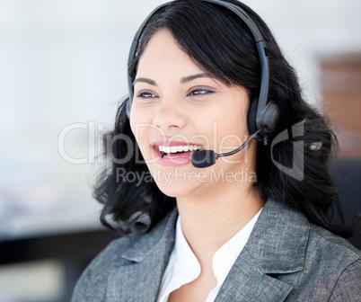 Joyful businesswoman wearing a headset to talk with customer