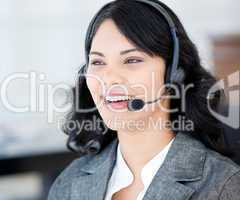 Joyful businesswoman wearing a headset to talk with customer