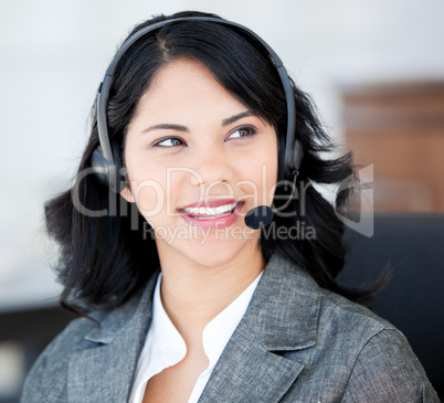 Attractive businesswoman wearing a headset to talk with customer
