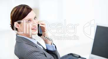 Smiling businesswoman on phone sitting at her desk