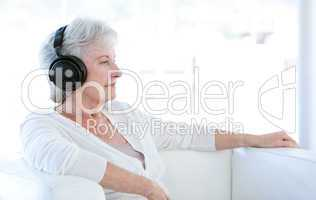 Senior woman listening music with headphones