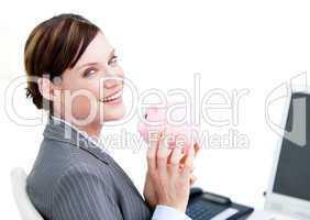 Cheerful businesswoman holding a piggy-bank