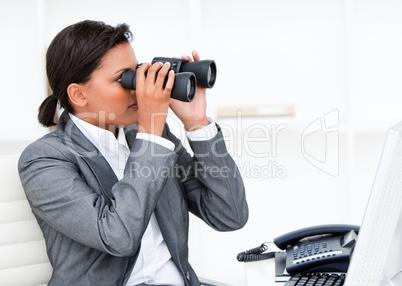 Self-assured businesswoman looking through binoculars