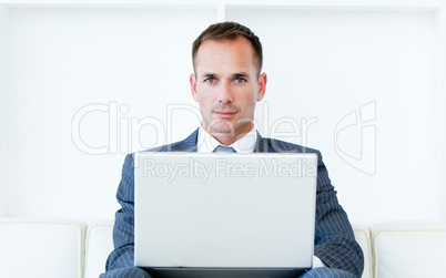 Confident businessman using a laptop sitting on a sofa