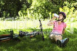 Teenage girl resting in a park with a bicycle