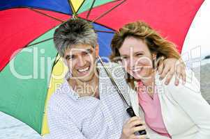 Happy mature couple with umbrella